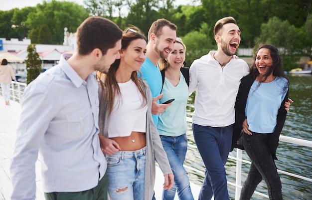 Groep glimlachende jonge en succesvolle mensen op vakantie op het dok. Premium Foto