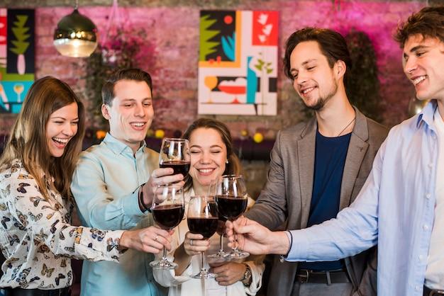 Groep glimlachende mannelijke en vrouwelijke vrienden die wijn in club roosteren Gratis Foto