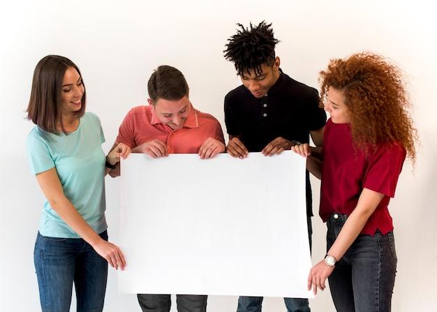 Groep glimlachende multi-etnische vrienden die leeg wit aanplakbiljet houden die zich op witte achtergrond bevinden Gratis Foto