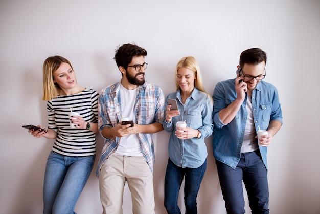 Groep jonge aantrekkelijke collegamensen die zich tegen de muur bevinden die mobiles controleren en koffie in document koppen voor een onderbreking drinken. Premium Foto