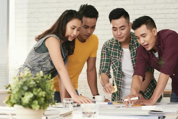 Groep jonge aziatische collega's die zich rond lijst bevinden en iets bekijken Gratis Foto