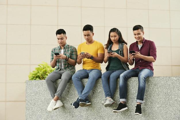 Groep jonge aziatische mensen die in straat zitten en smartphones gebruiken Gratis Foto
