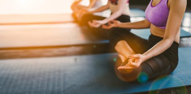 Groep jonge aziatische vrouwen sportieve aantrekkelijke mensen die yogales met instructeur uitoefenen. Premium Foto