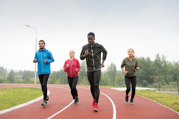Groep jonge interculturele sporters en sportvrouwen die deelnemen aan de marathon- of sprintwedstrijd op het stadion Premium Foto