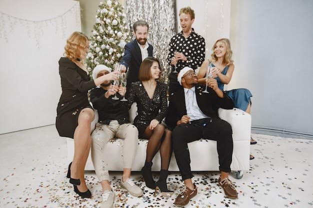 Groep jonge mensen die nieuw jaar vieren. vrienden drinken champagne. Gratis Foto