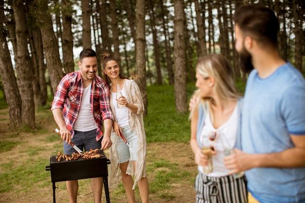 Groep jonge mensen die van barbecuepartij genieten in de aard Premium Foto