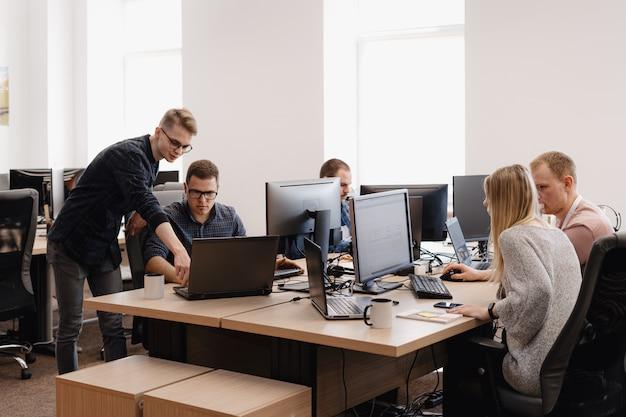 Groep jonge mensen uit het bedrijfsleven die werkzaam zijn in het kantoor Gratis Foto