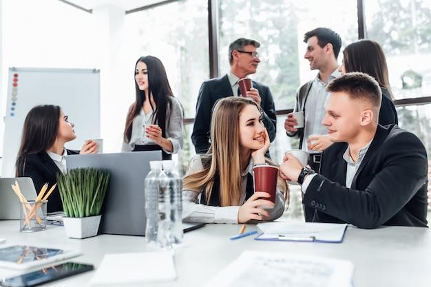Groep jonge mensen uit het bedrijfsleven op pauze in het kantoor. succesvol commercieel team dat op koffiepauze spreekt. Premium Foto