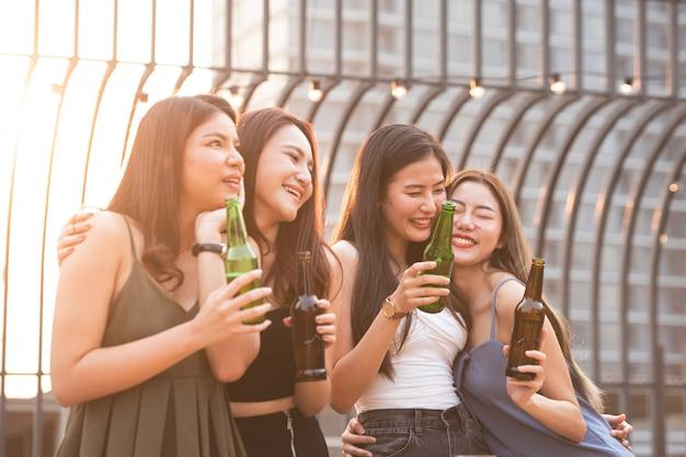 Groep jonge mooie gelukkige aziatische vrouwen die fles bierpraatje samen met vrienden houden terwijl het vieren van danspartij op openluchtdaknachtclub met exemplaarruimte voor reclame. Premium Foto