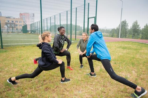 Groep jonge multiculturele vriendelijke mensen doen rekoefening voor benen op groen gras in natuurlijke omgeving Premium Foto