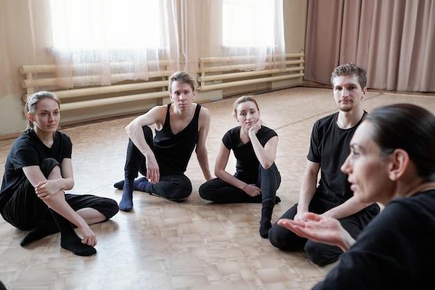 Groep jonge passen mannen en vrouwen in zwarte activewear zittend op de vloer en luisteren naar hun instructeur van studio dansen Premium Foto