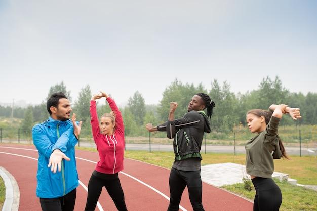 Groep jonge sportieve interculturele vrienden in activewear die opwarmingsoefeningen op stadion doen alvorens marathon te lopen Premium Foto