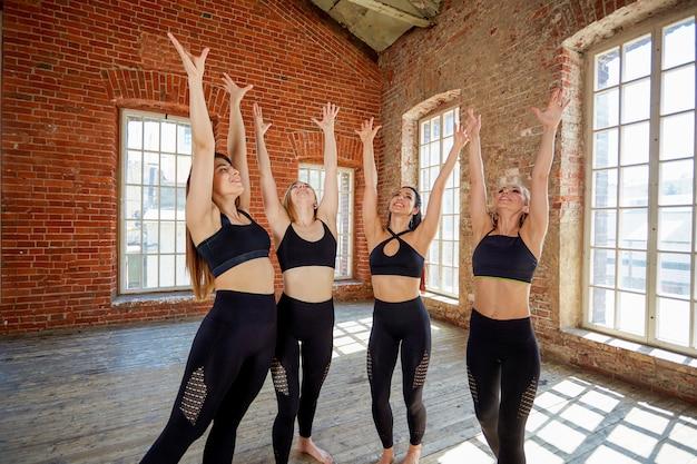 Groep jonge sportmeisjes die na een training in een ruime zolderstudio rusten. Premium Foto
