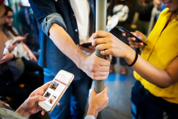 Groep jonge volwassen vrienden die smartphones in de metro gebruiken Gratis Foto