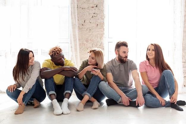 Groep jonge vrienden die op vloer zitten Gratis Foto