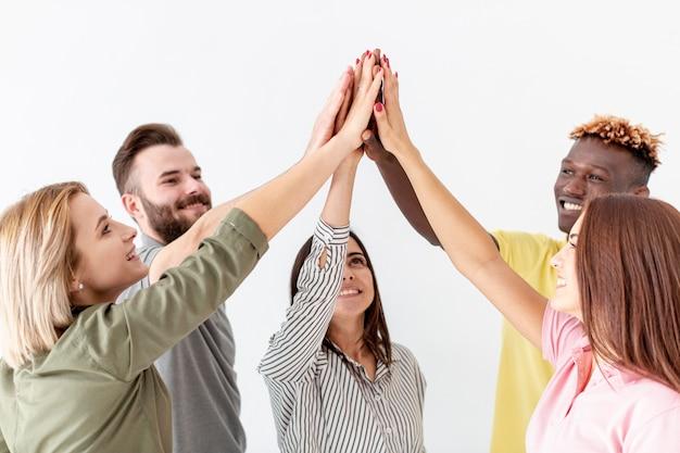 Groep jonge vrienden hoge vijf in de lucht Gratis Foto