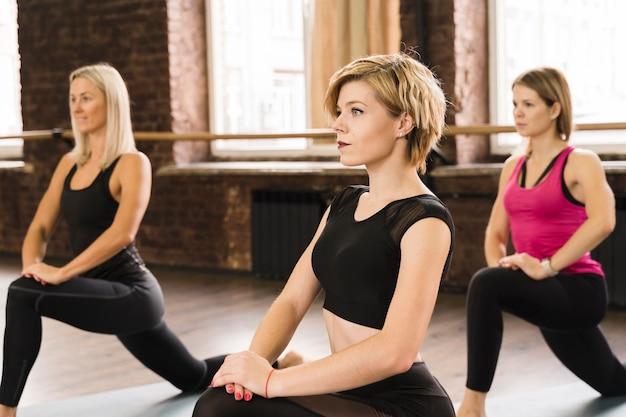Groep jonge vrouwen die bij de gymnastiek uitwerken Gratis Foto