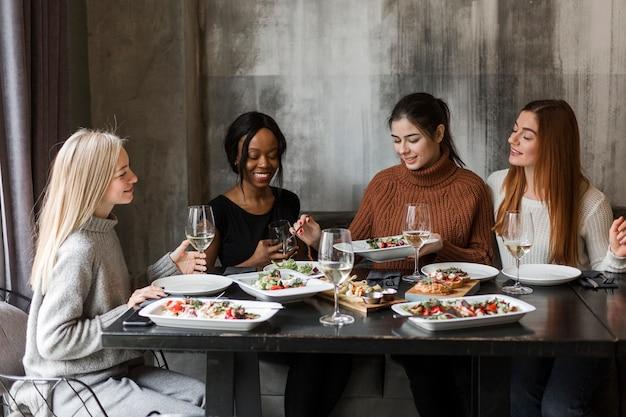 Groep jonge vrouwen die diner en wijn hebben samen Gratis Foto