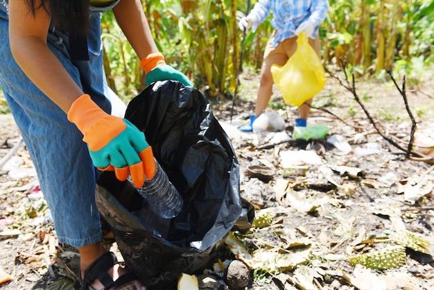 Groep jonge vrouwenvrijwilligers die aard helpen schoon houden en het huisvuil van park opnemen Premium Foto