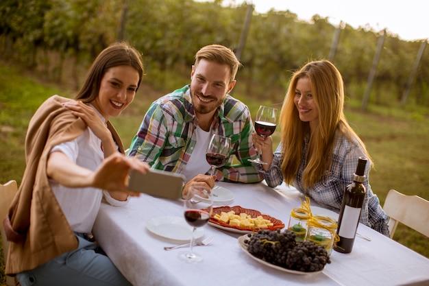 Groep jongeren die door de lijst zitten en rode wijn in de wijngaard drinken Premium Foto