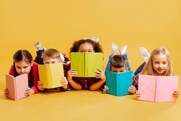 Groep kinderen die hun gezichten behandelen met boeken Gratis Foto