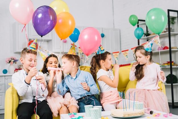 Groep kinderen die op bank zitten die kleurrijke ballons houden en partijhoorn blazen Gratis Foto