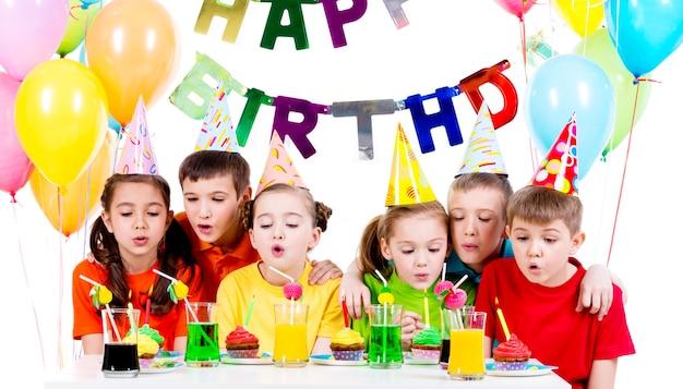 Groep kinderen in kleurrijke shirts blaast kaarsen op het verjaardagsfeestje - geïsoleerd op een witte. Gratis Foto
