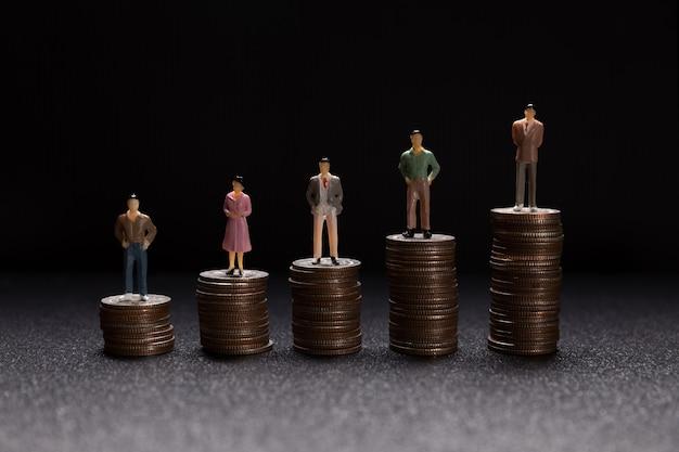 Groep kleine zakenlieden die zich op muntstukken bevinden Gratis Foto