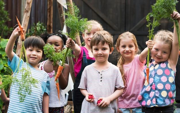 Groep kleuterschooljonge geitjes die tuinierend in openlucht leren Premium Foto