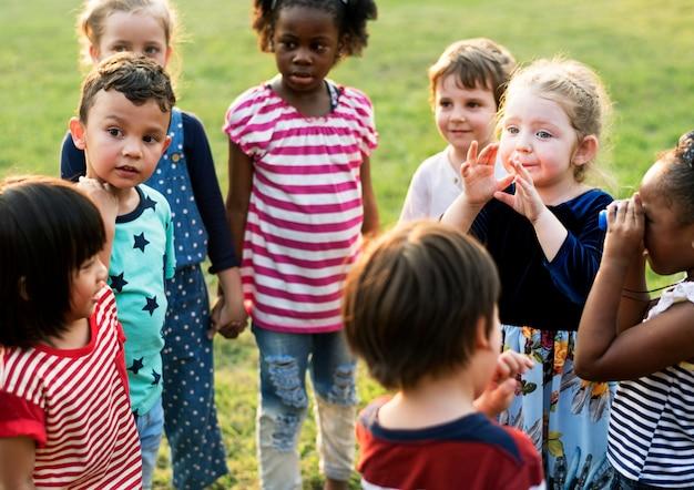 Groep kleuterschooljonge geitjesvrienden die handen houden die bij park spelen Premium Foto
