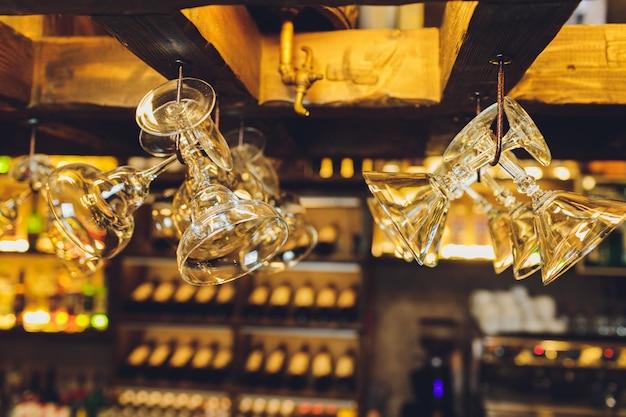 Groep lege wijnglazen die van metaalstralen hangen in een bar. Premium Foto