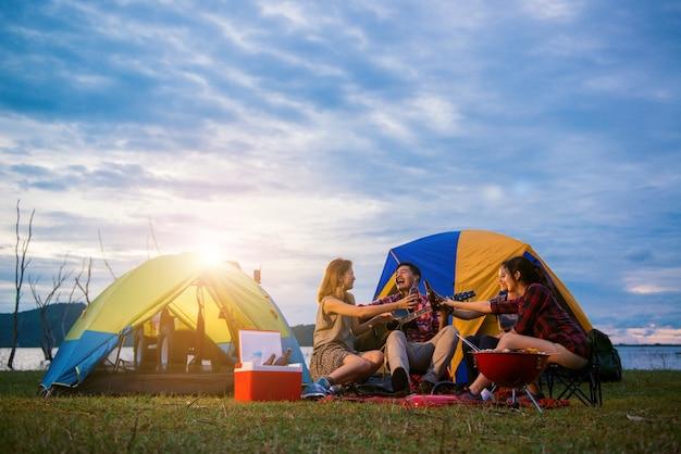 Groep man en vrouw genieten van camping picknick en barbecue bij het meer met tenten op de achtergrond. jonge gemengd ras aziatische vrouw en man. de handen van jonge mensen roosteren en juichen flessen bier. Gratis Foto