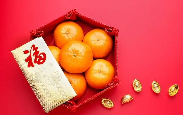 Groep mandarijn in dienblad en enveloppak ang pow met gouden baren op rood lijstbovenkant Premium Foto