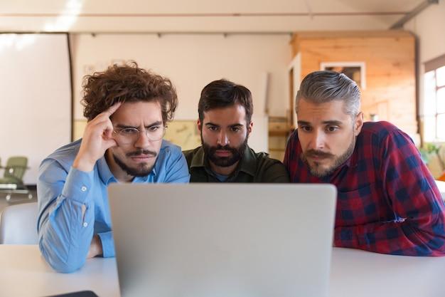 Groep mannelijke ondernemers in casual staren naar laptop monitor Gratis Foto