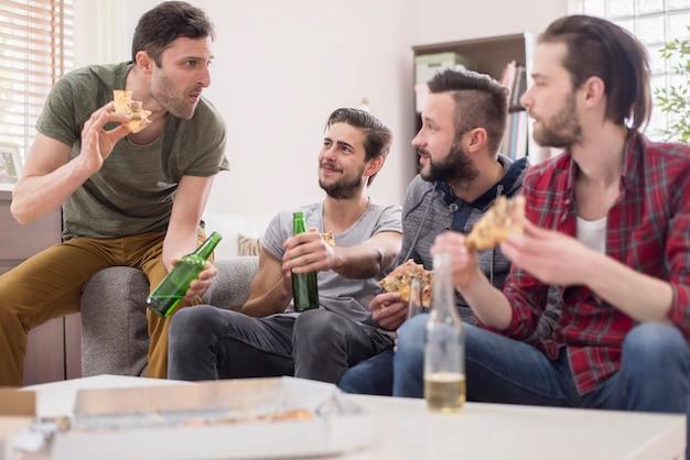 Groep mannen die pizza eten en een biertje drinken Gratis Foto