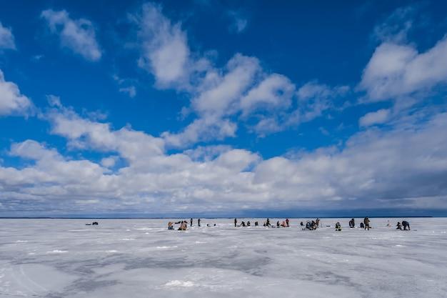 Groep mannen vissers die in de winter op het ijs van de rivier vissen Premium Foto