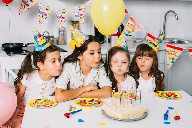 Groep meisjes die kaarsen op verjaardagscake blazen Gratis Foto