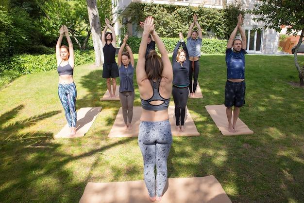 Groep mensen die yoga doen dichtbij flatgebouw Gratis Foto