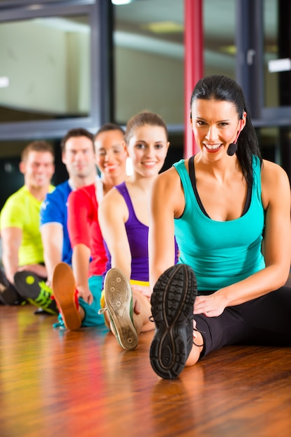 Groep mensen en instructeur in zich gymnastiek het uitrekken Premium Foto
