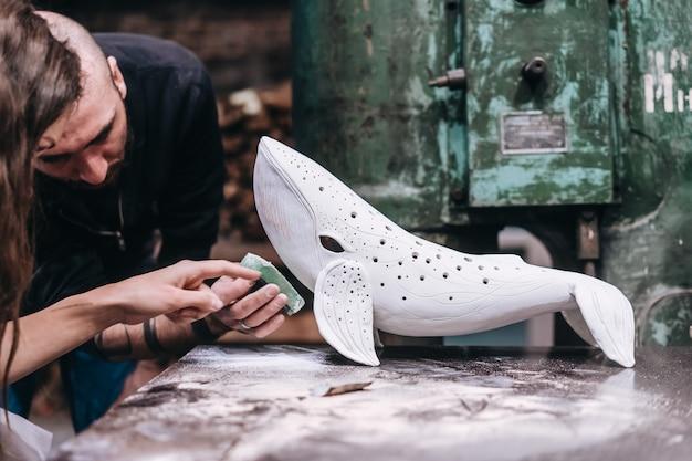 Groep mensen genieten van favoriete baan in werkplaats. mensen werken zorgvuldig aan keramische walvissen Gratis Foto