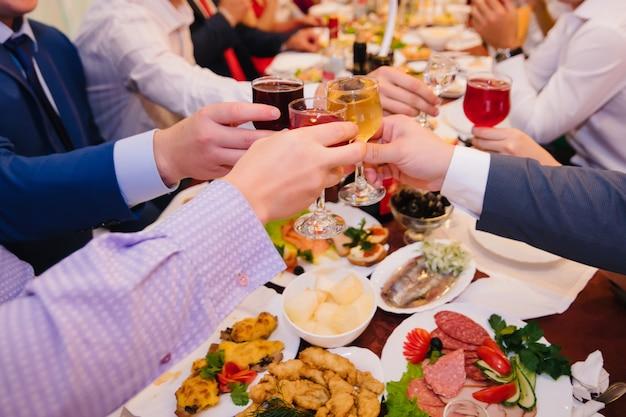 Groep mensen gerinkel glazen wijn in het restaurant Premium Foto