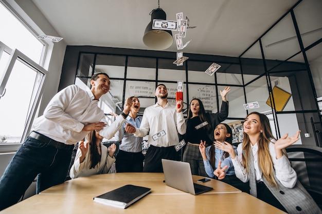Groep mensen gooien geld in een kantoor Gratis Foto