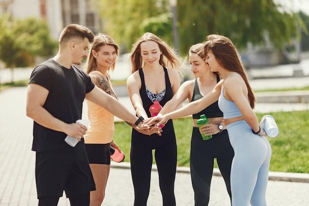 Groep mensen in een park. jongen met vier meisjes. sporters met flessen water. Gratis Foto
