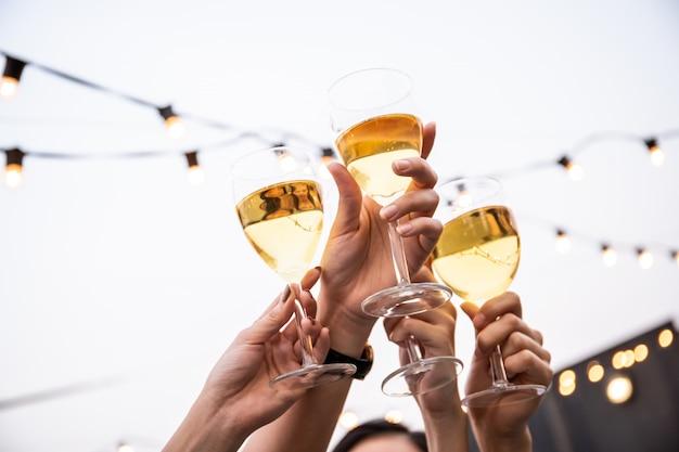 Groep mensen in feest en vieren samen met witte wijn Premium Foto