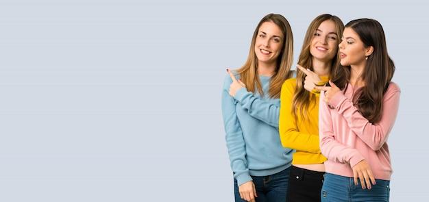 Groep mensen met kleurrijke kleding wijzend naar de kant om een product te presenteren Premium Foto