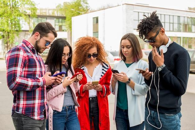 Groep moderne vrienden die cellphone gebruiken bij openlucht Gratis Foto