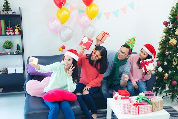 Groep multi-etnische medewerkers die selfie in kerstmanhoeden nemen bij bureaupartij, Premium Foto