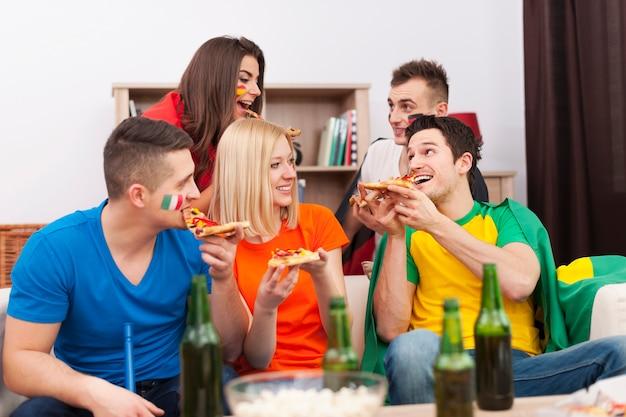 Groep multinationale mensen pizza eten tijdens de pauze in voetbalwedstrijd Gratis Foto