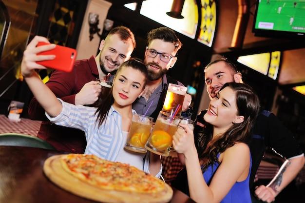 Groep of gezelschap van jonge mensen - vrienden drinken bier, eten pizza, praten en lachen en schieten selfie op de camera van de smartphone op het oppervlak van de bar Premium Foto