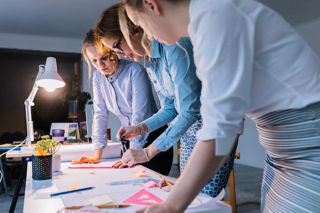 Groep onderneemsters die plan op witboek met instrumenten over bureau trekken op het werk Gratis Foto